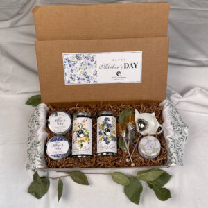 Mother's Day Tea Gift Box Set with a Stainless Steel Heart-Shaped Tea Infuser, 1 Candle, 1 Teapot-Shaped Bowl, 2 Honey Lollipop Tea Sweeteners, 2 Mini Tins, and 2 Tall Tins in the flavors of Blueberry Cobbler Rooibos Herbal Tea and Tahitian Vanilla Rose Oolong Tea